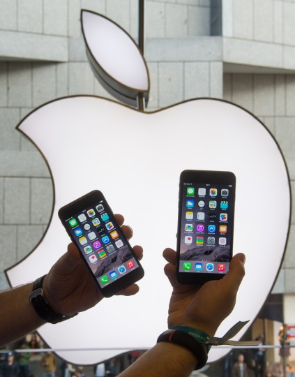 A man holds two new Iphone 6 mobile devices in front of a logo of Apple in Munich, southern Germany, on September 19, 2014 to purchase a new Apple Iphone 6 mobile device. Apple said earlier this week that it had received record pre-orders for its new iPhone models, and that some customers will have to wait for the larger-screen versions of the smartphones. Peter Kneffel/AFP/Getty Images