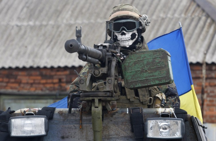A Ukrainian serviceman wears a mask depicting a skull on armored personnel carrier (APC) in a suburb of the eastern town Debaltseve in the region of Donetsk. Top UN human rights official Ivan Simonovic said on September 23 that the death toll in Ukraine's conflict has soared past 3,000, likely by a significant margin. (Anatolii Stepanov/Getty Images)
