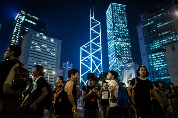 "Pro-democracy demonstrators check their smart phones in the central district as they gather for the third night in Hong Kong on September 30, 2014. The demonstrators have demanded full universal suffrage after Beijing said it would allow elections for the semi-autonomous city's next leader in 2017 but would vet the candidates -- a decision branded a ""fake democracy"". (Philippe Lopez/AFP/Getty Images)"
