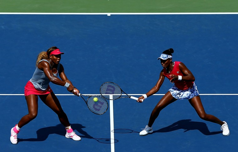 Venus Williams (R) and Serena Williams (L) of the United States return a shot against Ekaterina Makarova and Elena Vesnina of Russia during their women's doubles quarterfinal match on Day Nine of the 2014 US Open at the USTA Billie Jean King National Tennis Center on September 2, 2014 in the Flushing neighborhood of the Queens borough of New York City. (Getty Images/Elsa)
