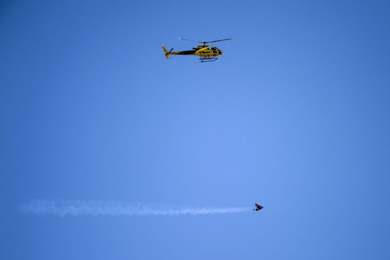 """Swiss pilot Yves Rossy known as the """"Jetman"""" flights beneath a helicopter with his jet-powered two meters wingspan wing attached to his back during the first day of the AIR14 air show on August 30, 2014 in Payerne, western Switzerland. (FABRICE COFFRINI/AFP/Getty Images)"""