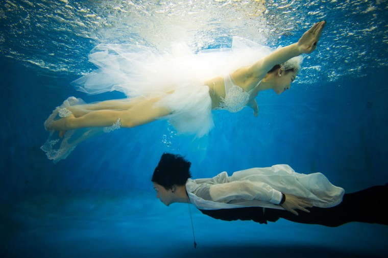 Qin Riyang (bottom) and Leng Yuting, both 26 years old, posing underwater for their wedding pictures at a photo studio in Shanghai, ahead of their wedding next year. (Johannes Eisele/AFP/Getty Images)