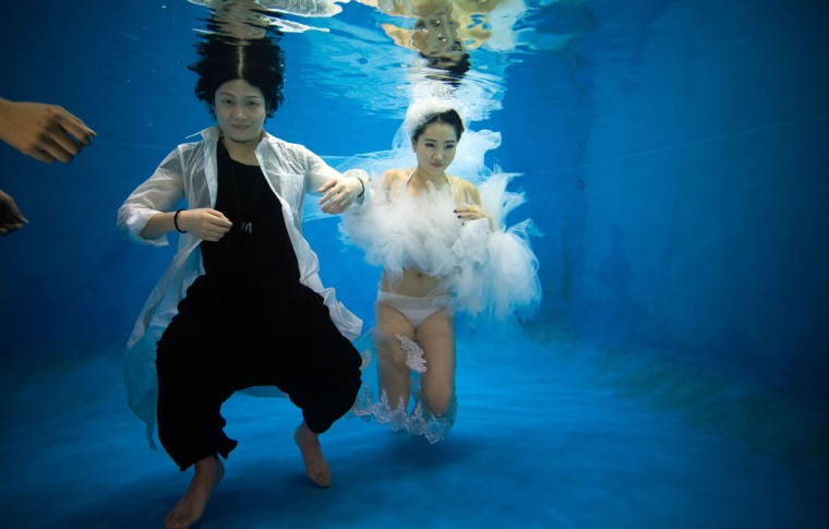 Qin Riyang (L) and Leng Yuting, both 26 years old, posing underwater for their wedding pictures at a photo studio in Shanghai, ahead of their wedding next year. (Johannes Eisele/AFP/Getty Images)