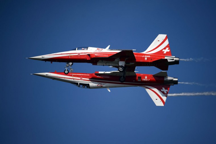 """Two fighter jets of the """"Patrouille Suisse"""" (Swiss patrol) perform the """"mirror"""" formation during the second week-end of the AIR14 air show on September 6, 2014 in Payerne, western Switzerland. (FABRICE COFFRINI/AFP/Getty Images)"""