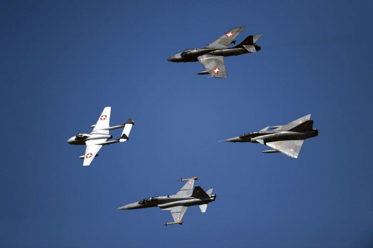 """Former fighter jets of the Swiss Air Force, the """"De Havilland Vampire"""" (left), the """"Hawker Hunter"""" (above), the """"Northrop F-5 Tiger"""" (Bellow), and the """"Dassault Mirage III"""" (right) perform during the second weekend of the AIR14 air show on September 6, 2014 in Payerne, western Switzerland. (FABRICE COFFRINI/AFP/Getty Images)"""