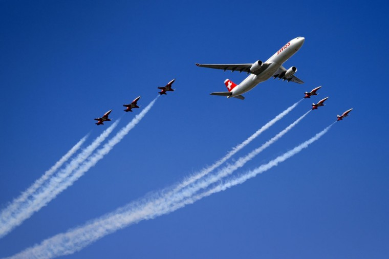 """An Airbus A330 commercial plane of Swiss International Air Lines flies with fighter jets of the """"Patrouille Suisse"""" (Swiss patrol) during the second weekend of the AIR14 air show on September 6, 2014 in Payerne, western Switzerland. (FABRICE COFFRINI/AFP/Getty Images)"""