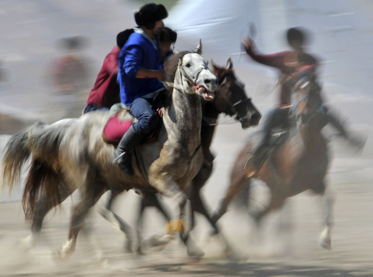 Kyrgyz (blue) and Turkish (red) riders play the traditional Central Asian sport Buzkashi also known as Kok-Boru or Oglak Tartis in the first World Nomad Games in Cholpon-Ata, some 270 km from Bishkek on September 12, 2014 . Mounted players compete for points by throwing a stuffed sheepskin into a well. (Vyacheslav Oseledkov/AFP/Getty Images)