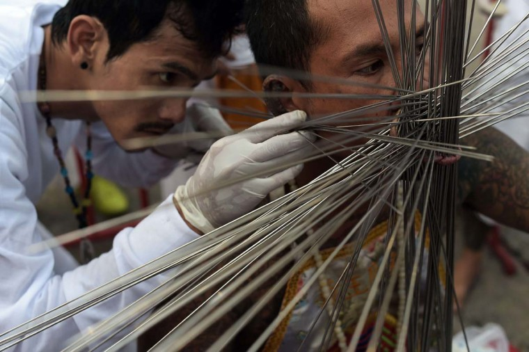A devotee of the Chinese Bang Neow Shrine has metal rods inserted into his cheeks ahead of a street procession during the annual Vegetarian Festival in the southern Thai town of Phuket on September 29, 2014. During the festival, which begins on the first evening of the ninth lunar month and lasts nine days, religious devotees slash themselves with swords, pierce their cheeks with sharp objects and commit other painful acts to purify themselves, taking on the sins of the community. (Christophe Archambault/AFP/Getty Images)