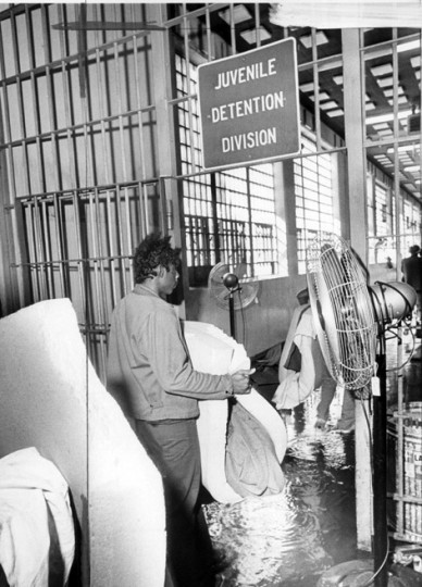 An inmate carries bedding through a puddle of water at the Baltimore city jail early in the morning after 150 rioting prisoners caused $30,000 in damage, including the commissary. (Weyman Swagger/Baltimore Sun file/Feb. 26, 1973)
