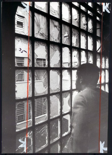 A City Jail inmate looks out through block windows smashed during the disturbance. (George H. Cook/Baltimore Sun file/Feb. 18, 1971)