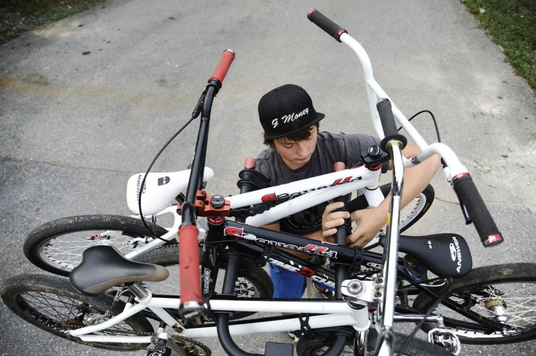 Grant Raum, 14, of Clear Spring, lifts one of his family's bikes on the rack on the back of his family's truck before they drive to Pottstown, PA for the Quaker State National races. The Raum family drove from Clear Spring together to stay the weekend in PA and compete in the races. Rachel Woolf/Baltimore Sun