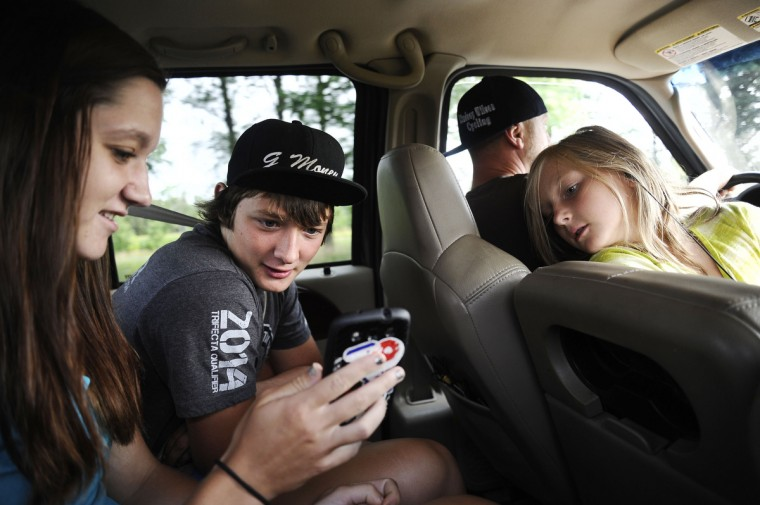 From left, Ashton Raum, 19, sits in the car and looks at videos with her brother, Grant Raum, 14, as their dad, Timm Raum drives and Lilly Raum, 11, looks over the seat. The Raum family drove from Clear Spring together to stay the weekend in Pottstown, PA and compete in the Quaker State National races. Rachel Woolf/Baltimore Sun