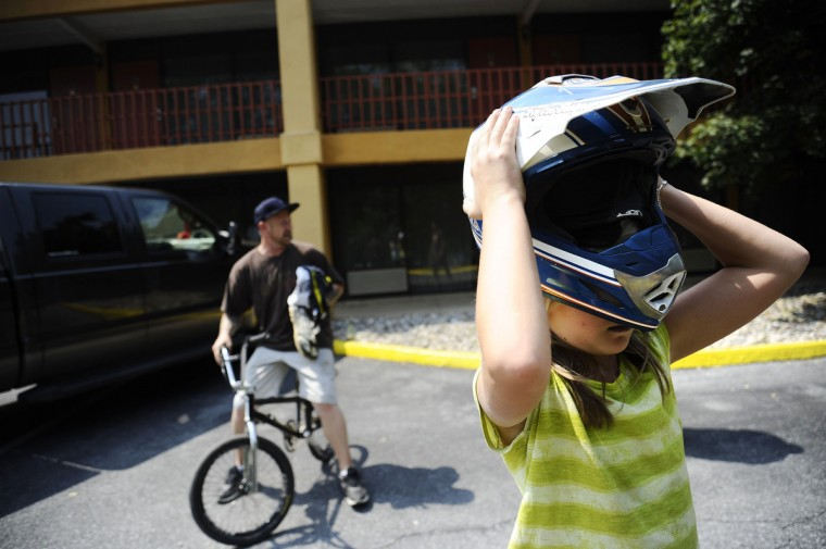 From left, Timm Raum sits on his bike while his daughter Lilly Raum, 11, tries on her dad's helmet in front of the hotel they're staying in next to the Quaker State National races in Pottstown, PA. Rachel Woolf/Baltimore Sun