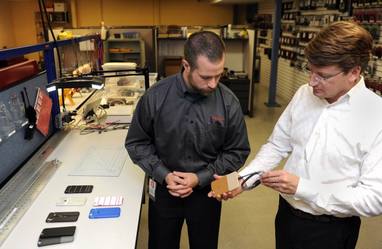 "Dave Schweitzer, left, quality manager for Ventev Mobile, checks the fit of power cable going into a ""Penna"" leather case his company manufactured to fit the new iPhone 6, which was just released today. He and other employees at Ventev Mobile, a division of TESSCO, checked out the new iPhone for the first time today to see if it fits in the cases (and other accessories) that the company manufactures. Scott Franklin, head of marketing for TESSCO, is on right. (Barbara Haddock Taylor, Baltimore Sun)"