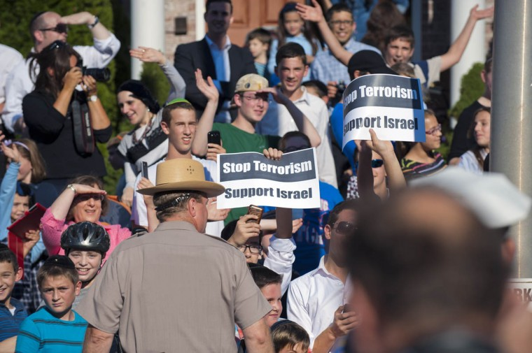 People hold signs as well as wave and smile as the motorcade for President Barack Obama heads for a private residence during a visit of the president to the city area and Fort McHenry Friday, Sep 12, 2014. (Karl Merton Ferron / Baltimore Sun)