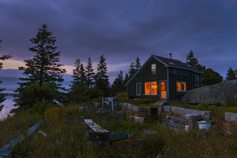 Resting behind the ruins of an old building long since gone, a home uses candlelight as its only source of light on the off-the-grid, privately-owned Dix Island, Maine, which once was the site of the Dix Island Granite Company. (Karl Merton Ferron/Baltimore Sun)