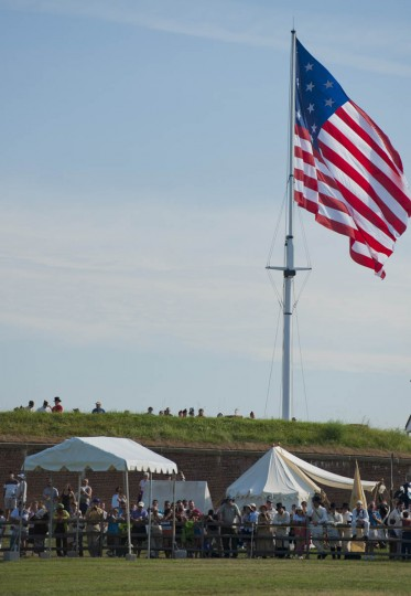 Visitors watch the scurrying of official and media during a visit of the president to the city and Fort McHenry Friday, Sep 12, 2014. (Karl Merton Ferron / Baltimore Sun)