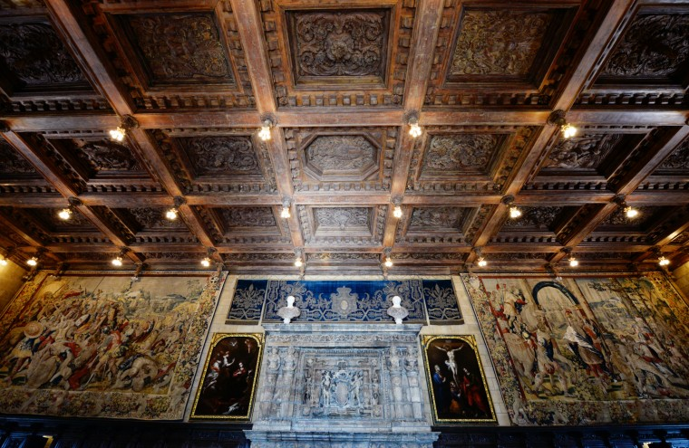 A large room in the Hearst Castle hosts elaborate ceiling designs and tapestries.
