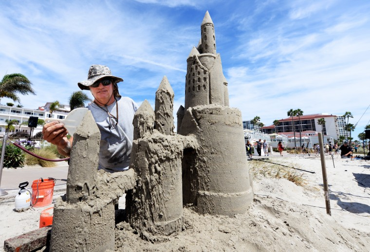 A sculptor creates a sand castle on the beach property in front of the Hotel del Coronado.