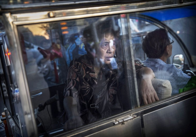 A Chinese woman waits in the back of a three-wheeled taxi while sitting in traffic during rush hour in Beijing, China. (Kevin Frayer/Getty Images)