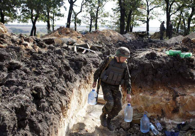 "A Ukrainian serviceman carries bottles of water to a position near the eastern town of Pervomaysk in the district of Lugansk. Ukrainian leader Petro Poroshenko will cast Russia as a global menace on September 18 when he meets US President Barack Obama in the hope of winning a ""special status"" guaranteeing his troubled nation's security. (Anatoli Stepanov/Getty Images)"
