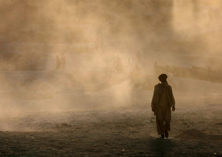 An Afghan man walks amidst a dust cloud as the sun sets in Kabul. (Mohammad Ismail/Reuters)