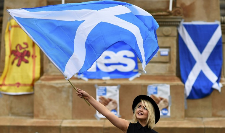 A woman waves a Scottish Saltire at a 'Yes' campaign rally in Glasgow, Scotland. The referendum on Scottish independence will take place, when Scotland will vote whether or not to end the 307-year-old union with the rest of the United Kingdom. (Dylan Martinez/Reuters)