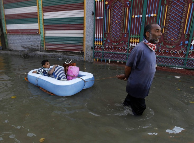 A Kashmir man pulls an inflatable raft carrying a boy through a flooded neighborhood in Srinagar. Both the Indian and Pakistani sides of the disputed Himalayan region have seen extensive flooding this month with Srinagar particularly hard hit. Hundreds of people have been killed and tens of thousands are homeless. (Danish Ismail/Reuters)
