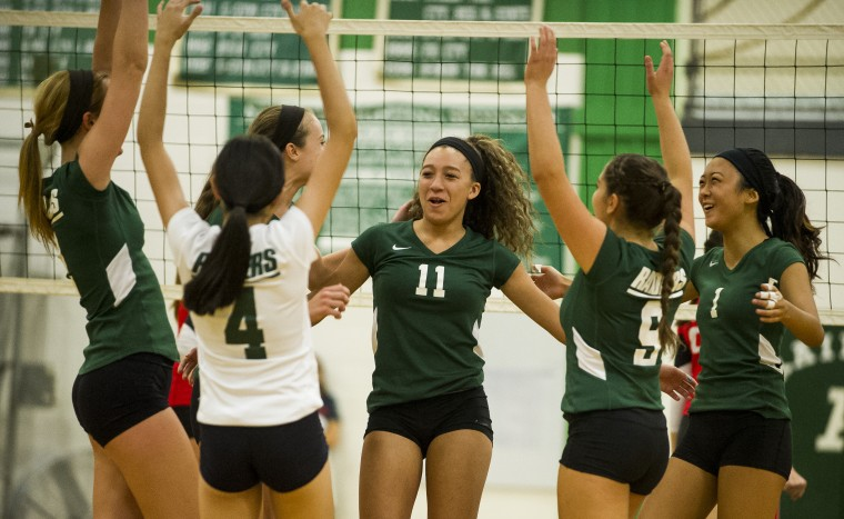 Teammates congratulate Chelsea Mitchell, center, after a block during the Glenelg vs. Atholton volleyball match in Columbia Monday, Sept. 15. Glenelg defeated Atholton is four sets. (Photo by Scott Serio, Baltimore Sun Media Group)