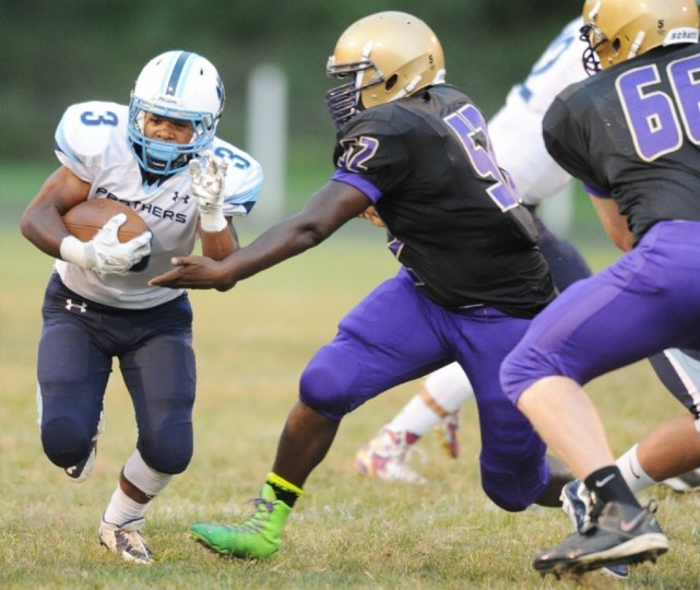 Pallotti's Jaret Patterson takes a hand off past Loch Raven's Donyell Lipscomb during the Panthers' 56-7 victory in Towson Friday, Sept. 19. (Staff photo by Brian Krista, Baltimore Sun Media Group)
