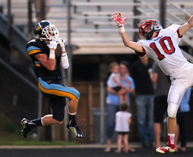 River Hill's Chuck Mclaughlin, left, makes a catch while being pressured bt Glenelg's Brett Wasson, right, during the football game at River Hill High School in Clarksville on Friday, Sept. 5, 2014. (Jen Rynda/BSMG)