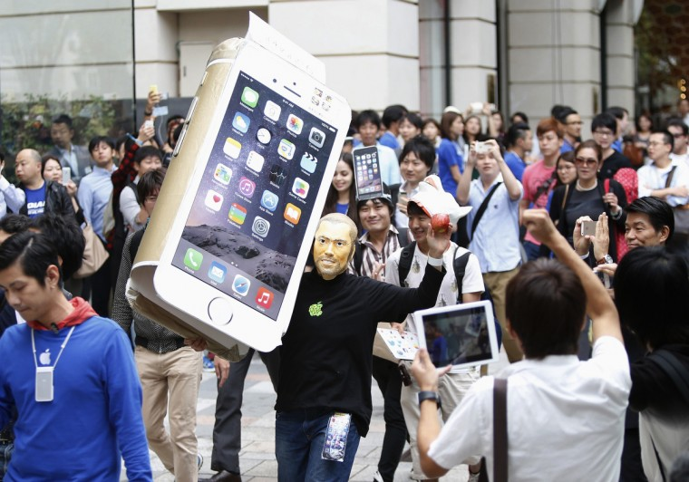 A man wearing a mask depicting Apple's co-founder Steve Jobs holds up a cardboard cut-out of Apple's new iPhone 6, as he walks into the Apple Store at Tokyo's Omotesando shopping district September 19, 2014. Yuya Shino/Reuters photo