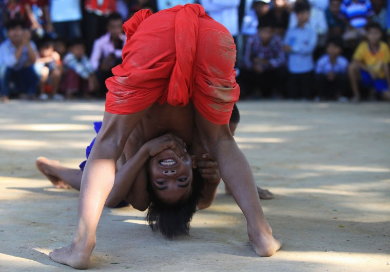 Boys wrestle during an annual buffalo-racing ceremony at Virhear Sour village in Kandal province September 23, 2014. The ceremony, which started more than 70 years ago, is held to honour the Neakta Preah Srok pagoda spirit. It also marks the end of the Festival of Pchum Ben. (Samrang Pring/Reuters)