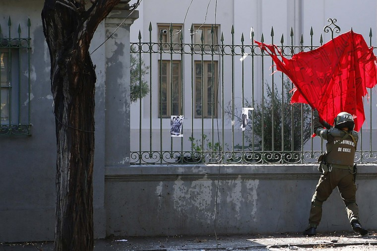 A riot police removes a flag from a fence at a high school during a protest in Santiago September 10, 2014. Chilean students have demanded changes and an end to profiteering in the education system. (van Alvarado/Reuters)