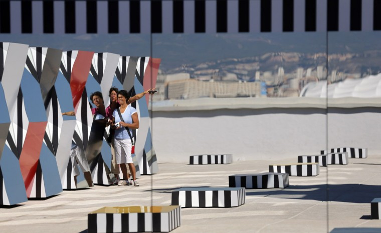 "Visitors are reflected in a creation as part of the exhibition ""Defini Fini Infini, Travaux in situ"" by French artist Daniel Buren at the MaMo art center in Marseille September 12, 2014. (Photos by Jean-Paul Pelissier/Reuters)"
