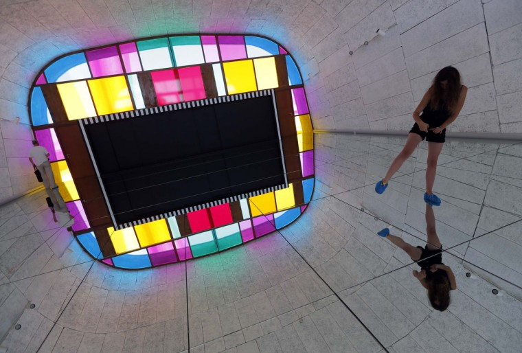 "A visitor takes a picture as she walks on a creation as part of the exhibition ""Defini Fini Infini, Travaux in situ"" by French artist Daniel Buren at the MaMo art center in Marseille September 12, 2014. (Photos by Jean-Paul Pelissier/Reuters)"