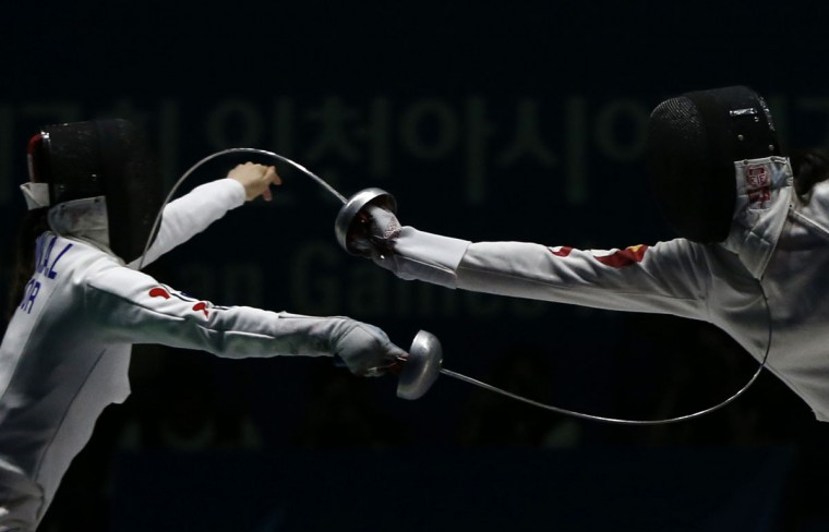 South Korea's Shin Alam (L) competes against China's Xu Anqi during their women's epee team fencing competition final at Goyang Gymnasium during the 17th Asian Games in Incheon September 25, 2014. (REUTERS/Issei Kato)