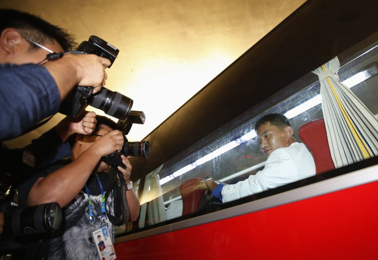 South Korean photographers take photographs of a member of North Korean contingent as they leave upon their arrival for the 17th Asian Games, at Incheon International Airport in Incheon September 11, 2014. REUTERS/Kim Hong-Ji