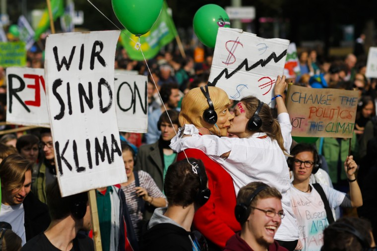A protester, posing as a lobbyist, kisses another wearing a mask of German Chancellor Angela Merkel during a Climate Change March in Berlin. The People's Climate March, a global action day organized ahead of next week's United Nations climate summit in New York, is demanding politicians take tougher action to protect the climate. (Thomas Peter/Reuters)