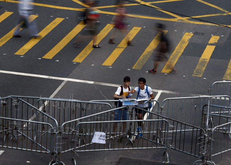 Men consult maps as the stand by a barricade at an area blocked by protesters near the government headquarters building in Hong Kong, September 30, 2014. Tens of thousands of pro-democracy protesters extended a blockade of Hong Kong streets on Tuesday, stockpiling supplies and erecting makeshift barricades ahead of what some fear may be a push by police to clear the roads before Chinese National Day. (Carlos Barria/Reuters)