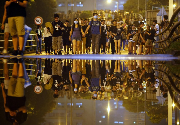 Protesters walk along a street as they block an area near the government headquarters building in Hong Kong September 30, 2014. Tens of thousands of pro-democracy protesters extended a blockade of Hong Kong streets on Tuesday, stockpiling supplies and erecting makeshift barricades ahead of what some fear may be a push by police to clear the roads before Chinese National Day. (Carlos Barria/Reuters)