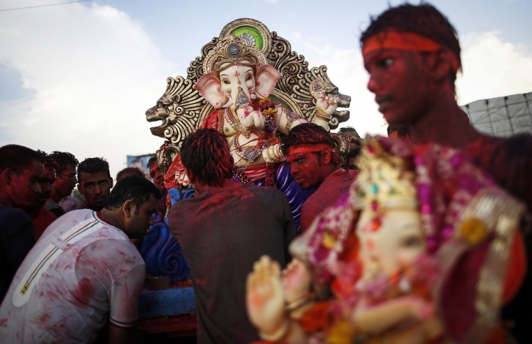 Devotees carry statues of the Hindu god Ganesh, the deity of prosperity, to be immersed into the Arabian Sea on the fifth day of the ten-day-long Ganesh Chaturthi festival in Mumbai September 2, 2014. Ganesh idols are taken through the streets in a procession accompanied by dancing and singing, and later immersed in a river or the sea, symbolising a ritual seeing-off of his journey towards his abode, taking away with him the misfortunes of all mankind. (REUTERS/Danish Siddiqui)