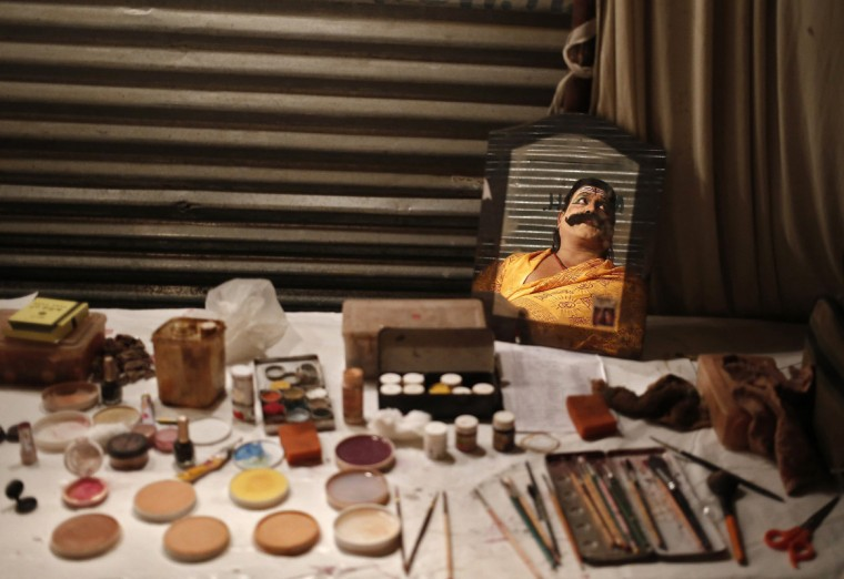"""An artist dressed as demon king Ravana is reflected in a mirror as a makeup kit lies backstage before his performance during Ramlila, a re-enactment of the life of Lord Rama, ahead of Dussehra in New Delhi September 23, 2014. Effigies of the 10-headed demon king """"Ravana"""" are burnt on Dussehra, the Hindu festival that commemorates the triumph of Lord Rama over the Ravana, marking the victory of good over evil. (Anindito Mukherjee/Reuters)"""