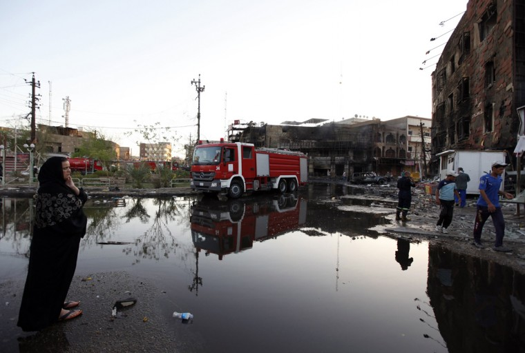 A woman looks at the site of a car bomb attack in Baghdad, September 11, 2014. REUTERS/Ahmed Saad