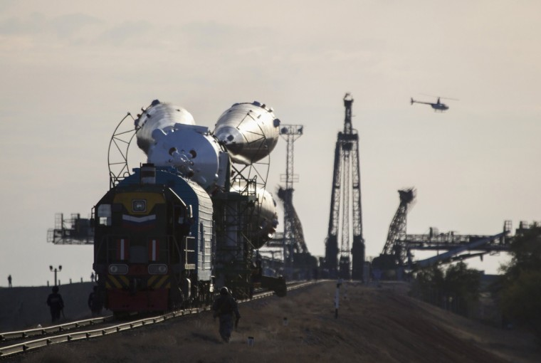 A helicopter flies past as the Soyuz TMA-14M spacecraft is transported to its launch pad at Baikonur cosmodrome September 23, 2014. The Soyuz is scheduled to carry Barry Wilmore of the U.S., Elena Serova and Alexander Samokutyaev of Russia to the International Space Station on September 26. (Shamil Zhumatov/Reuters)