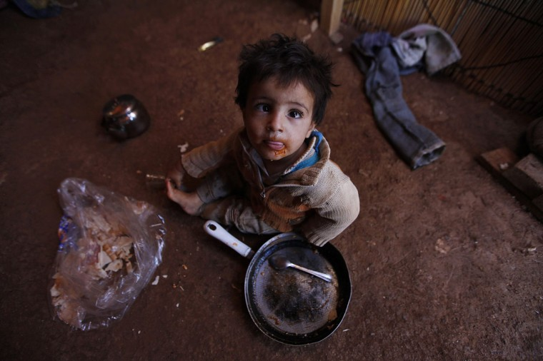A Syrian refugee child eats inside his family's tent at an informal settlement in Deir al-Ahmar, Bekaa valley September 16, 2014. Senior UN officials visited Syrian refugees, who now make up one-fourth of Lebanon's entire population, in the Bekaa region on Tuesday and called for the international community to assist the Lebanese government in dealing with the refugee crisis. (REUTERS/Alia Haju)