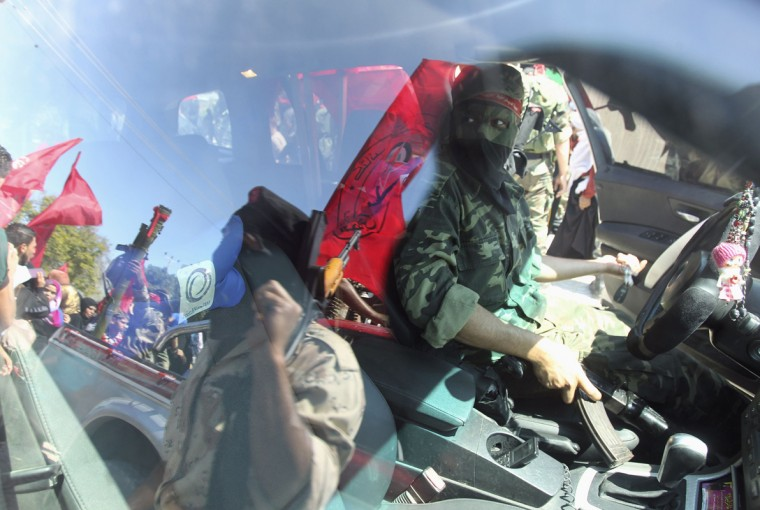 A Palestinian militant from the Democratic Front for the Liberation of Palestine (DFLP) ride in a vehicle as others are reflected in the window during a military show in Gaza City September 11, 2014. An open-ended ceasefire between Israel and Hamas-led Gaza militants, mediated by Egypt, took effect on August 26, 2014 after a seven-week conflict. It called for an indefinite halt to hostilities, the immediate opening of Gaza's blockaded crossings with Israel and Egypt, and a widening of the territory's fishing zone in the Mediterranean. REUTERS/Ahmed Zakot