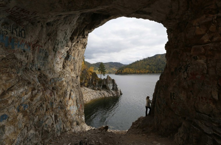 A tourist is seen through a hole in the Tsarskie Vorota (The Tsar Gate) rock on a bank of the Biryusa Gulf of the Yenisei River in the Taiga district outside Krasnoyarsk, Siberia, September 22, 2014. Picture taken September 22, 2014. (Ilya Naymushin/Reuters)