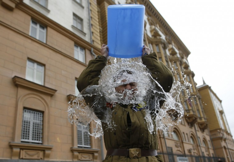 "Alexei Didenko, a deputy for the Russian State Duma, dumps a bucket of cold water on himself in front of the American embassy in Moscow. Didenko said he was performing the ice bucket challenge not only to raise awareness for ALS (Amyotrophic Lateral Sclerosis) research, but also to protest against new U.S. Ambassador to Russia John Tefft, and what Didenko calls ""anti-Russian American propaganda"". (Maxim Zmeyev/Reuters)"