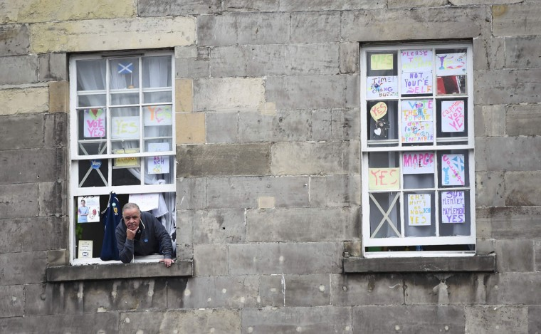 A man looks out of a window decorated with home-made pro-independence posters in Edinburgh, Scotland, September 16, 2014. The referendum on Scottish independence will take place on September 18, when Scotland will vote whether or not to end the 307-year-old union with the rest of the United Kingdom. (REUTERS/Dylan Martinez)